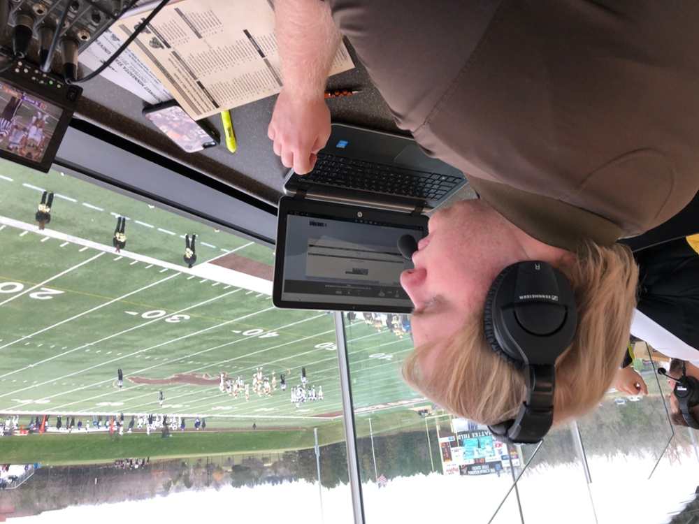 Matt Metzler doing the play-by-play in the press box at a Mustang Football game