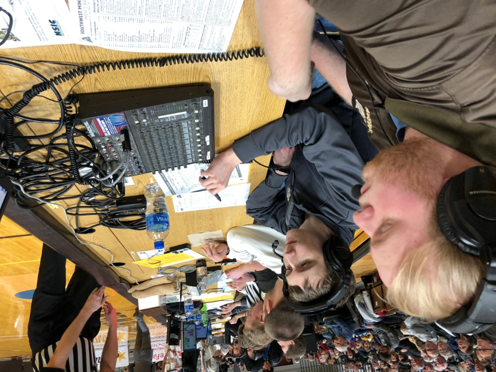 Students doing play-by-play court side at Mustang men's basketball