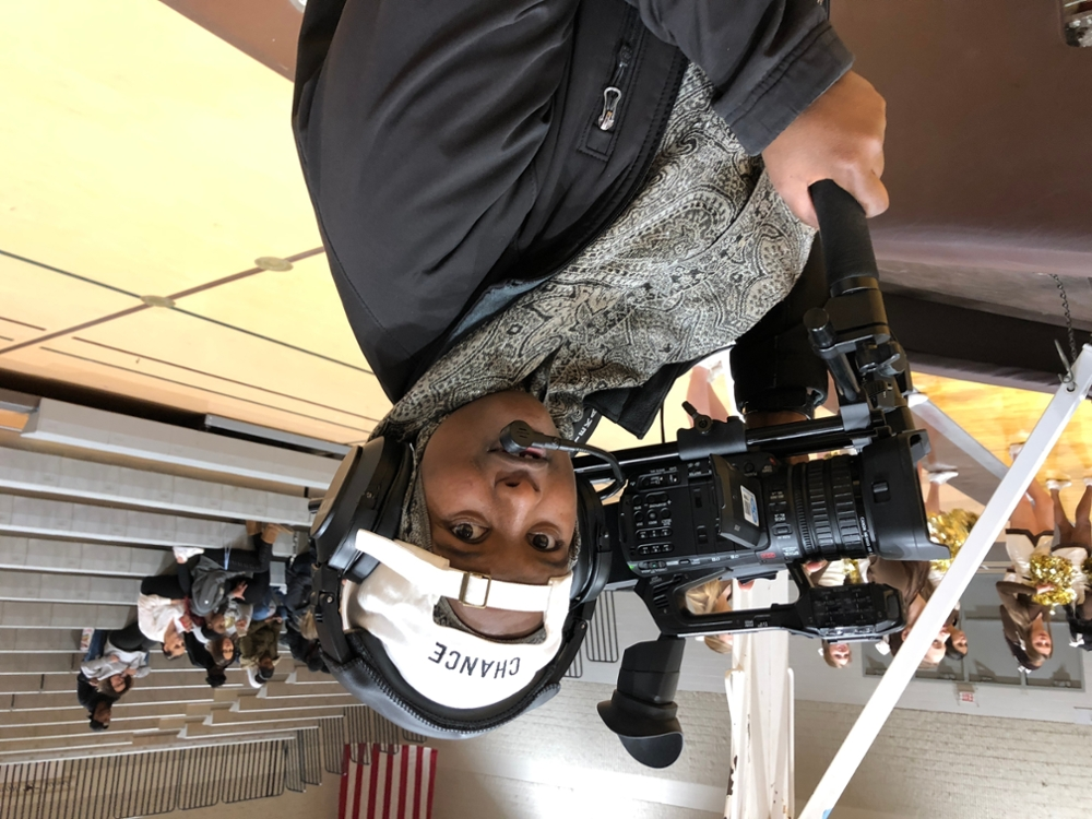Court side camera operator at the men's basketball game