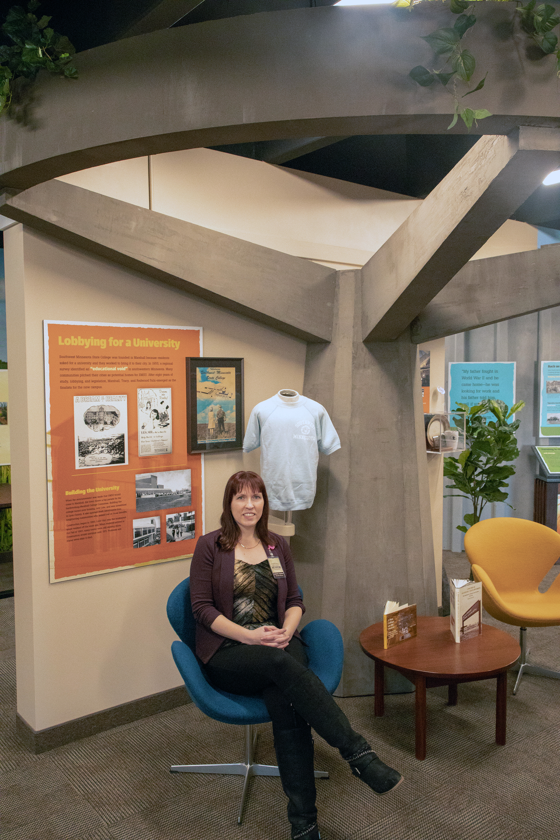 Jennifer Andries, sitting in the new SMSU display on the second floor of the Lyon County Historical Museum