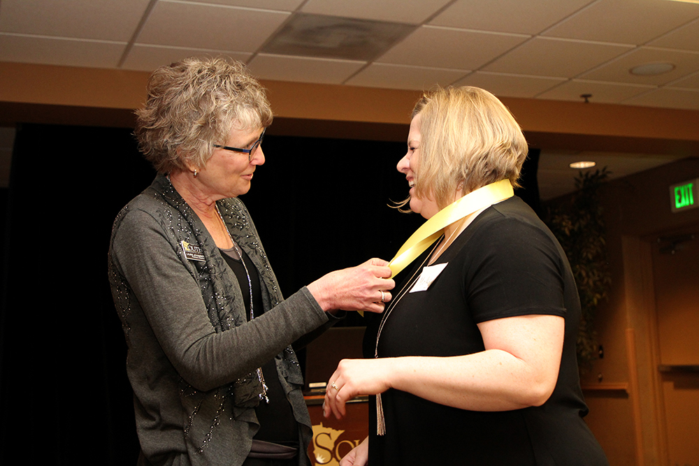 Laurie Johansen, left, pins an RN to BSN graduate. There are 150 alumni in the RN to BSN program.
